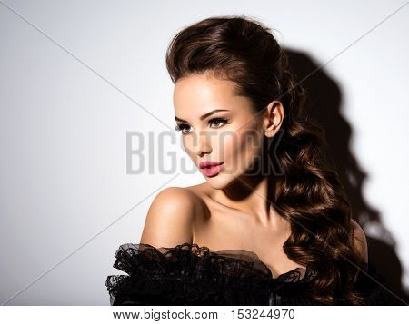 Beautiful face of an young sexy girl in black dress  posing at studio on white background