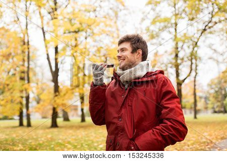 leisure, technology, communication and people concept - smiling hipster man using voice command recorder or calling on smartphone at autumn park