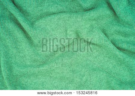 close up green knitted pullover background. Top view.