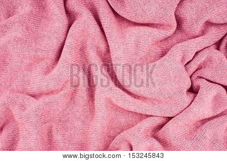 close up pink knitted pullover background. Top view.