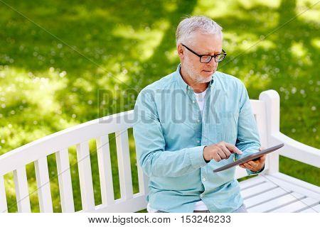 technology, senior people, and lifestyle, distance learning concept - old man with tablet pc computer at summer park