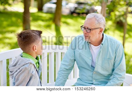 family, generation, communication and people concept - grandfather and grandson talking at summer park