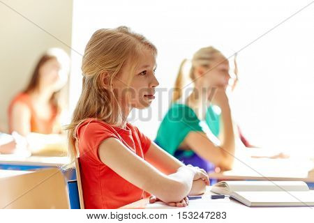 education, learning and people concept - group of students with notebooks at school lesson
