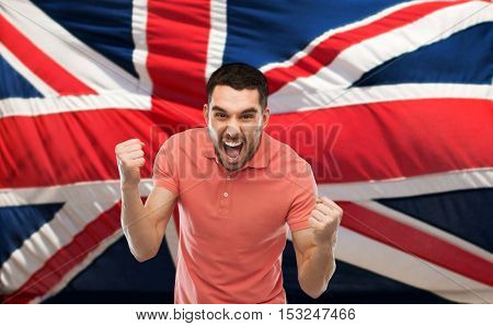 emotion, aggression, patriotism, gesture and people concept - angry young man showing fists and shouting over brittish flag