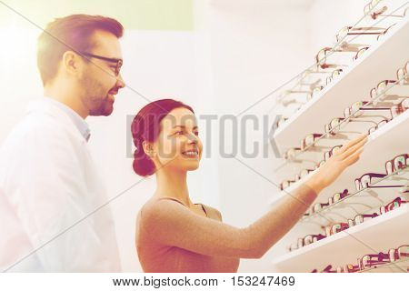 health care, people, eyesight and vision concept - happy woman choosing and showing glasses to optician at optics store