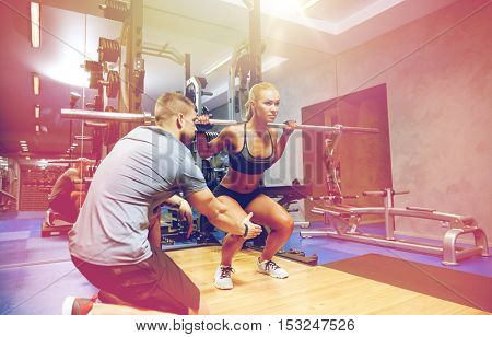 sport, fitness, teamwork, bodybuilding and people concept - young woman and personal trainer with barbell bar flexing muscles in gym