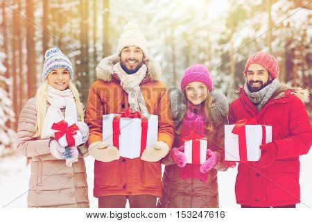 holidays, christmas, season, friendship and people concept - group of smiling friends with gift boxes in winter forest