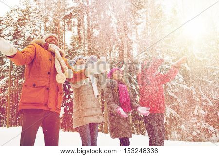 christmas, season, friendship and people concept - group of smiling men and women having fun and playing with snow in winter forest