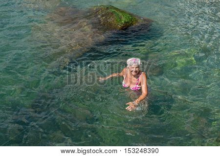 Aged Woman Is Standing In Clear Water Of Sea Shallow.