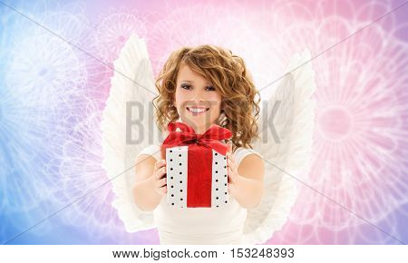 people, holidays and birthday concept - happy young woman with angel wings holding gift box over rose quartz and serenity pattern background