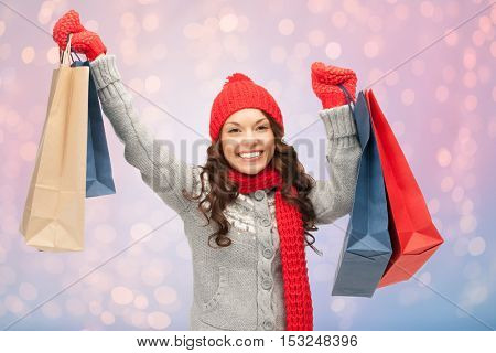 winter holidays, sale, christmas and people concept - smiling young woman in hat and mittens with shopping bags over rose quartz and serenity lights background
