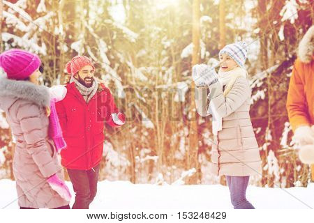 christmas, season, friendship and people concept - group of smiling men and women having fun and playing snowball game in winter forest