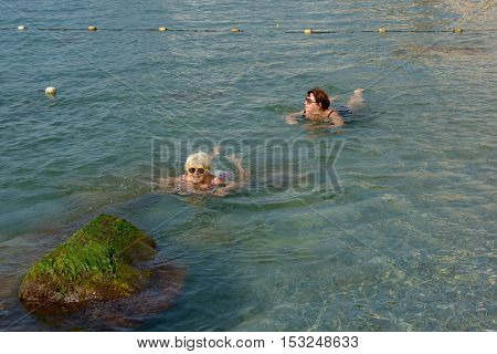 Two Women Are Swimming In Clear Water Of Sea Shallow.
