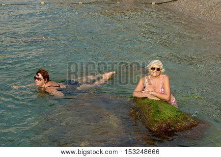 Two Women Are In Clear Water Of Sea Shallow.