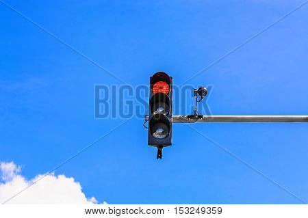 A traffic light and a surveillance camera on a pole mounted on the street.