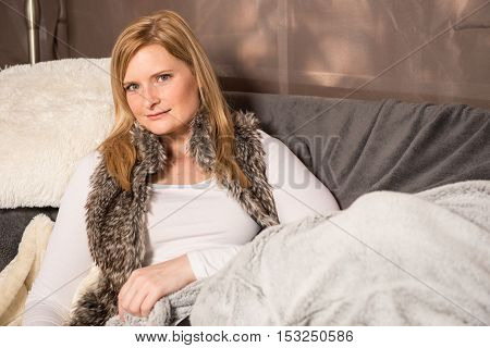 Attractive woman resting on a couch in the tent