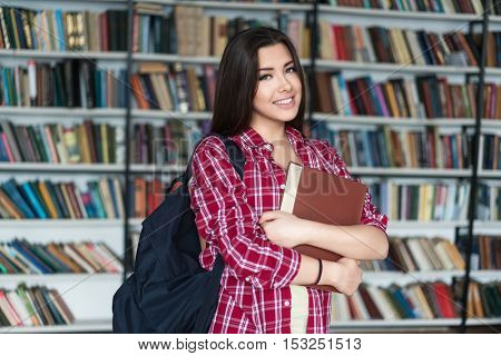Smiling woman with book in a library