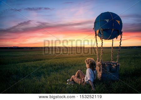 Little boy with aerostat in the field
