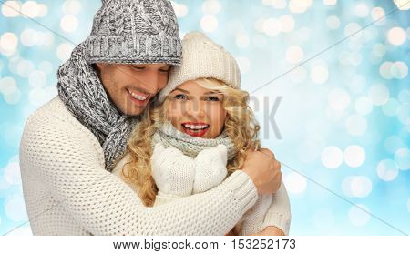 people, christmas, holidays and new year concept - happy family couple in winter clothes hugging over blue lights background