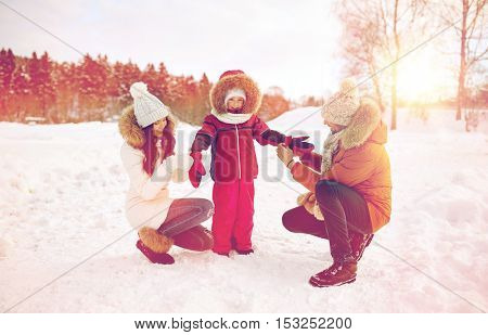 parenthood, fashion, season and people concept - happy family with child in winter clothes outdoors