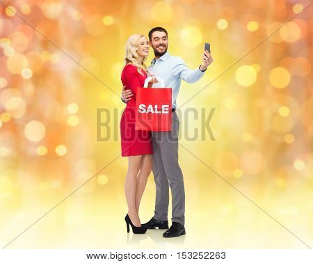 people, christmas, sale, technology and holidays concept - happy young woman and man with red shopping bag taking selfie by smartphone over lights background