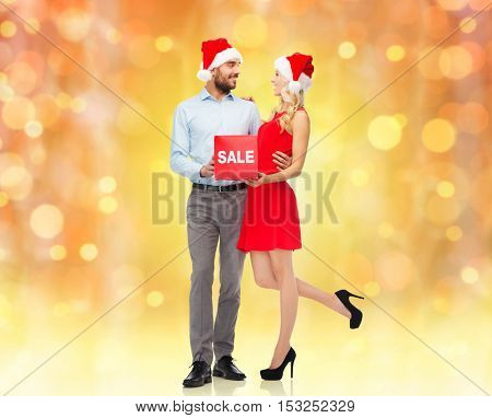 christmas, people, sale, discount and holidays concept - happy couple in santa hats with red sale sign over lights background