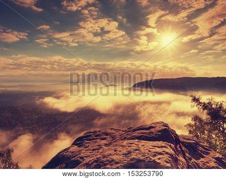 Blue Misty Daybreak. Sandstone Cliff Above Deep Foggy Valley In Mountains.
