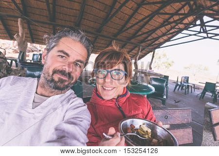 Couple taking selfie while having lunch in tourist resort toned image. Wilderness safari and adventure in Africa. Man with beard woman with eyeglasses.