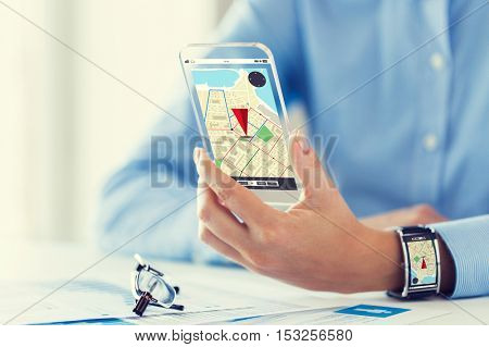 business, technology, navigation, location and people concept - close up of woman hand with gps navigator map on transparent smartphone and smart watch screen