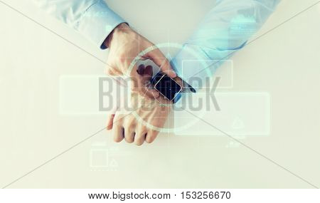 business, future technology and people concept - close up of male hands setting smart watch with virtual screens projection