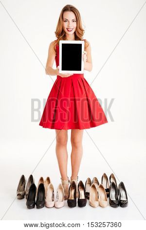 Portrait of a smiling young woman in red dress holding blank screen tablet computer and buying shoes isolated on a white background