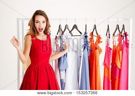 Portrait of a confused pretty woman standing at the rack with colorful clothes isolated on a white background