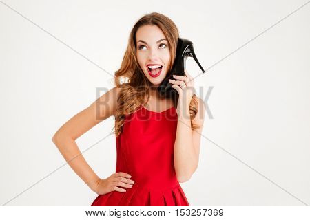 Portrait of a cheerful young woman in red dress holding high heels shoes at her ear isolated on a white background