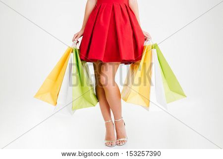 Cropped image of a woman in red dress and sandals holding colorful shopping bags isolated on a white background