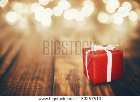 Red gift box and Christmas garland lights on wooden rustic background.