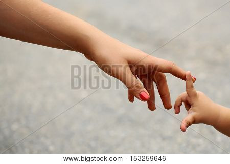 Little fragile baby hand touching mothers finger on gray background