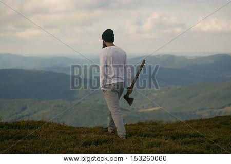 Handsome man bearded hipster with beard and moustache in hat stands with axe on mountain top on cloudy sky