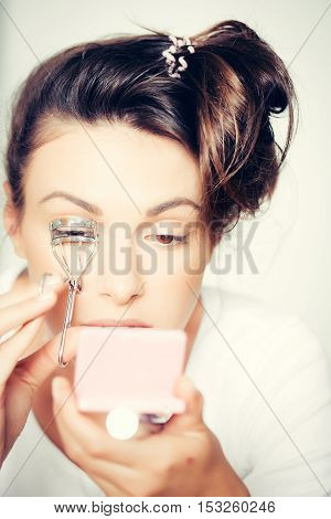 young cute sexy woman or girl portrait with pretty face and brunette hair curling eyelashes with tongs or forceps as fashionable makeup holding mirror on white background