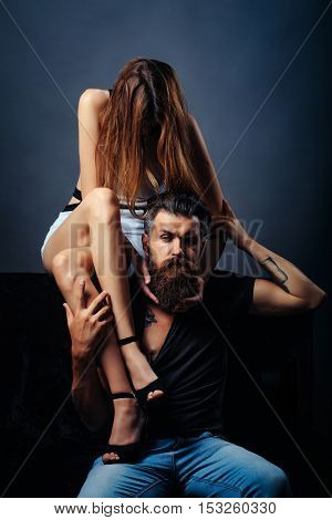 Pretty cute girl with sexy slim legs sits on shoulder of handsome bearded man hipster with long beard and moustache in studio on grey background