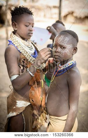 Kolcho Ethiopia - 18 August 2016: two unidentified boys from Karo tribe paint their face with natural colors and stick