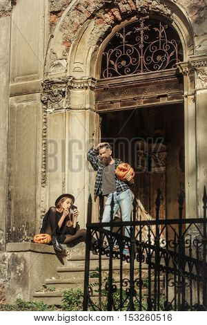 young halloween couple of bearded man with beard and mustache and girl in black witch hat near iron door of old ruined building with traditional autumn holiday symbol of orange spooky pumpkin outdoor