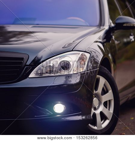 Headlights of dark blue car. Concept of expensive, sports auto.