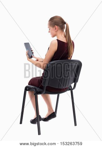 back view of woman sitting on chair and looks at the screen of the tablet.  Rear view people collection.  girl in a burgundy dress sitting on a chair and reading a phone.