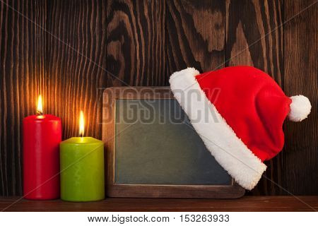 Christmas candles and chalkboard with santa hat. View with copy space