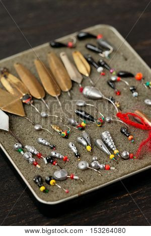 Set of old lures for ice fishing in tobacco box, close-up