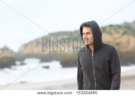 Portrait of a confident teenager walking on the beach in a rainy day