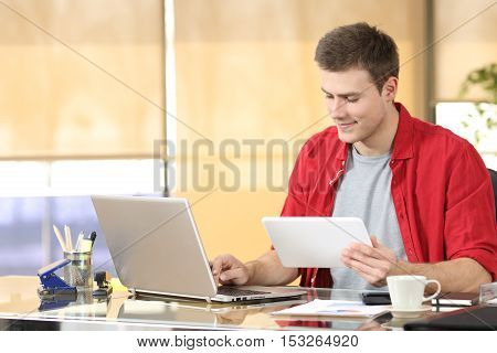 Portrait of a concentrated entrepreneur working on line with technology equipment sitting in a desktop at office