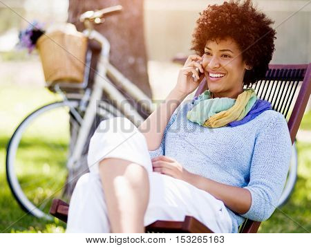 Charming young woman in summer park with mobile