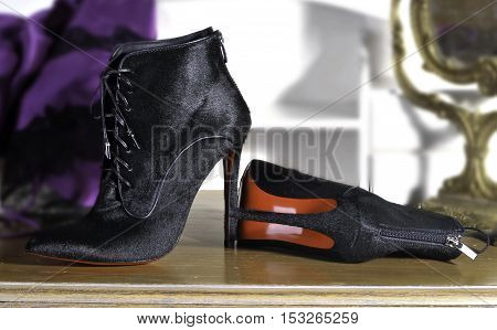 Ukraine Kiev - August 25 2016: Women's boots handmade. imitation brand shoes Christian Louboutin showing red soles - illustrative editorial