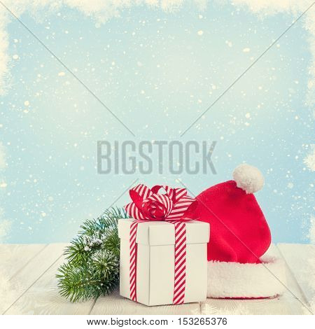 Christmas gift box, santa hat and fir tree branch on wooden table with background for copy space. Retro toned